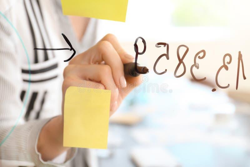 Vrouw die op transparante raad in conferentiezaal schrijven, close-up stock fotografie