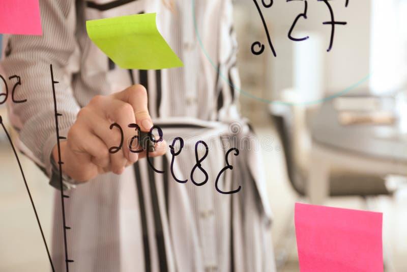 Vrouw die op transparante raad in conferentiezaal schrijven, close-up stock foto