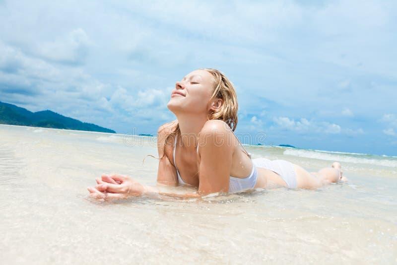Vrouw die op tropisch strand geniet van stock foto's