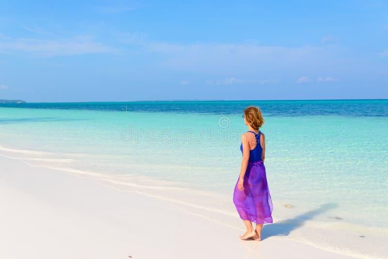 Vrouw die op tropisch strand lopen Achter overzeese van het het strand turkooise trasparent water van het menings witte zand Cara stock fotografie