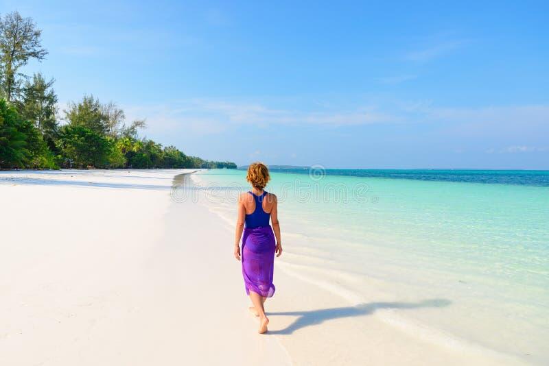 Vrouw die op tropisch strand lopen Achter overzeese van het het strand turkooise trasparent water van het menings witte zand Cara stock afbeeldingen