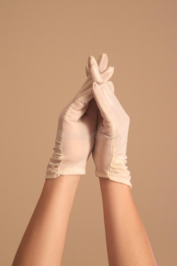 Vrouw die op uitstekende witte handschoenen met gekruiste vingers modelleren royalty-vrije stock fotografie