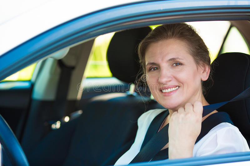 Vrouw die op veiligheidsgordel binnen haar auto trekken stock foto