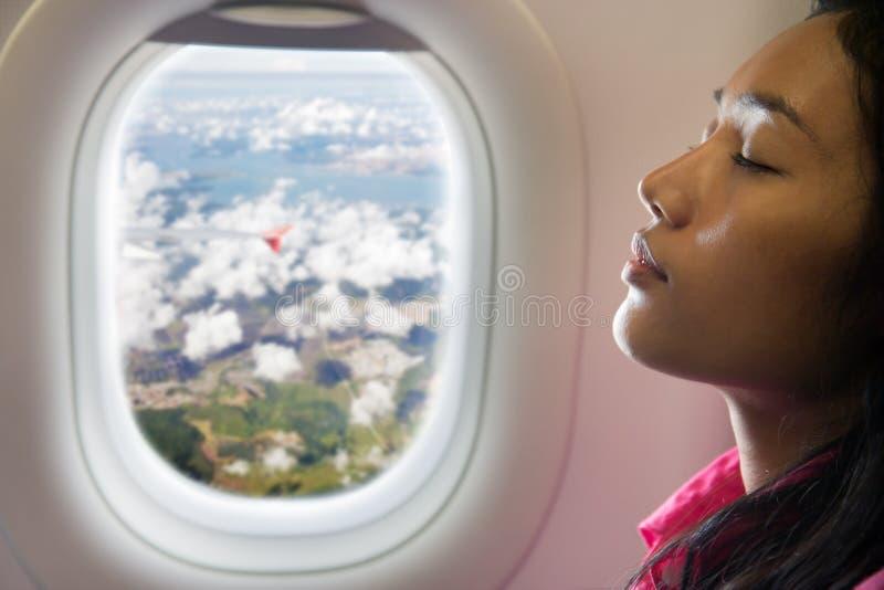 Vrouw die op vliegtuig rusten stock foto's