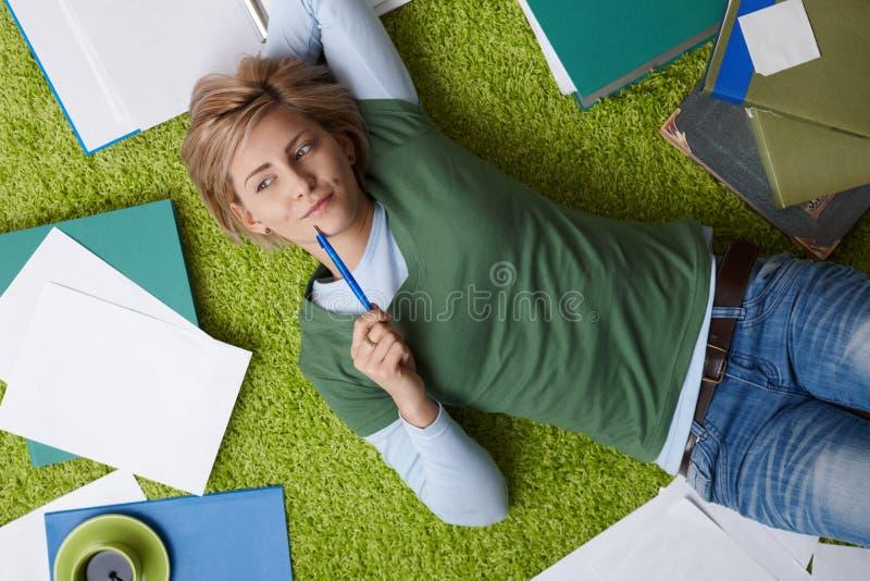 Vrouw die op vloer denkt royalty-vrije stock fotografie