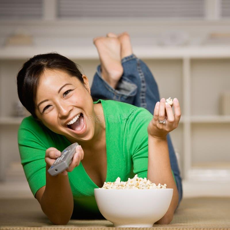 Vrouw die op vloer met kom popcorn legt royalty-vrije stock afbeeldingen
