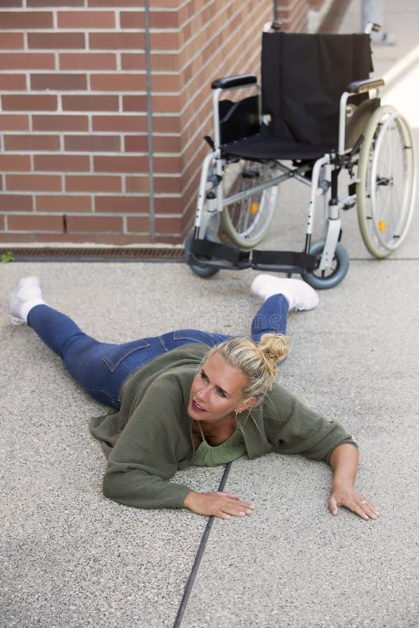Vrouw die op vloer naast rolstoel liggen royalty-vrije stock foto's