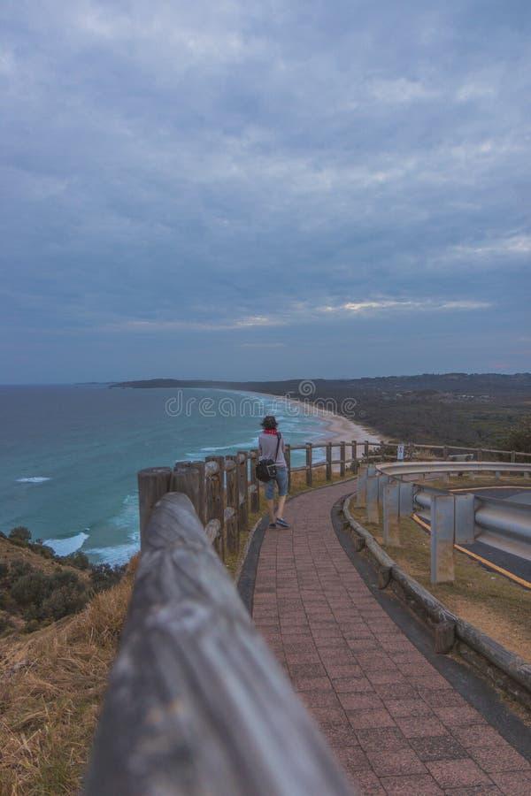 Vrouw die op weg van kust lopen stock foto
