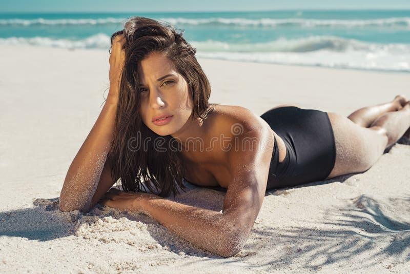 Vrouw die op wit zand liggen royalty-vrije stock foto