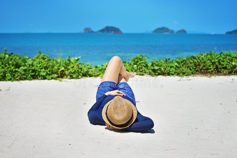 Vrouw die op wit zand in strandhoed leggen die van de zomer genieten stock fotografie