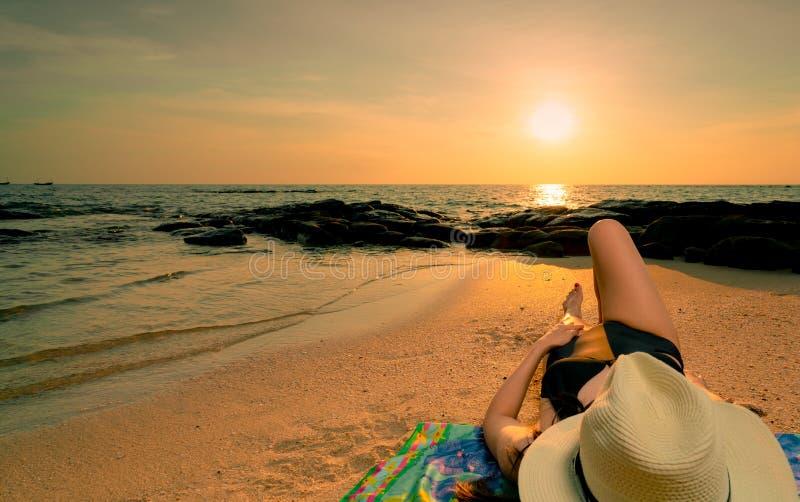 Vrouw die op zandstrand bij zonsopgang liggen Vrouw met strohoed die op tropisch paradijsstrand zonnebaden met mooie zonsopganghe royalty-vrije stock foto