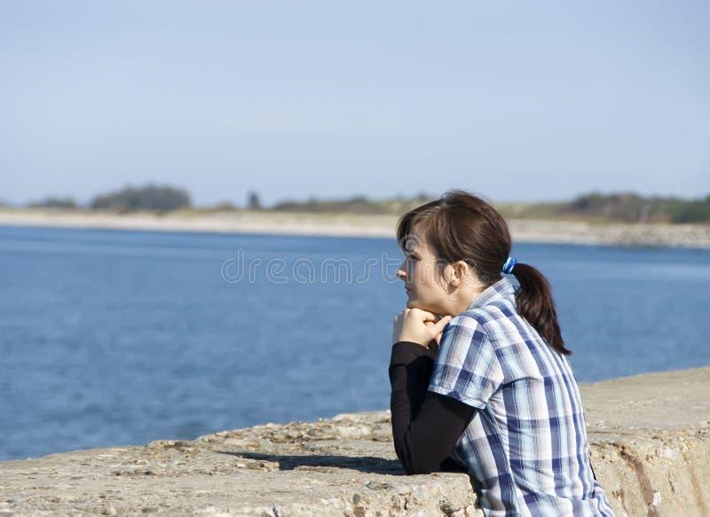 Vrouw die op zee kijkt stock fotografie