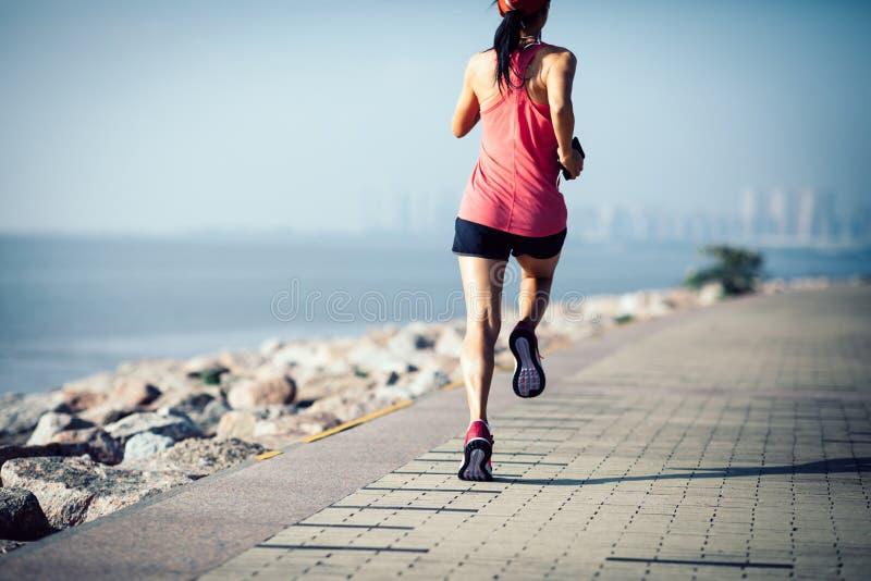 Vrouw die op zonnige kust lopen stock afbeelding