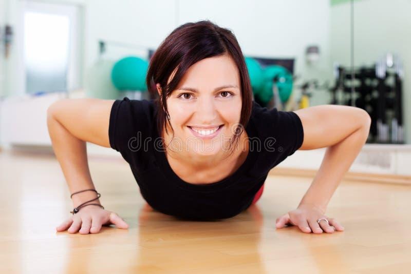 Vrouw die opdrukoefeningen in een gymnastiek doen stock foto's