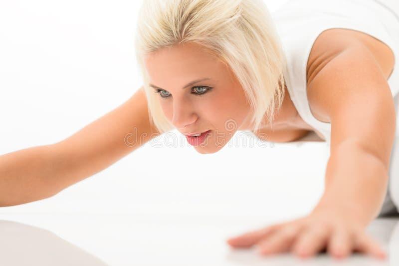 Vrouw die opdrukoefeningenoefening op witte vloer doet stock foto