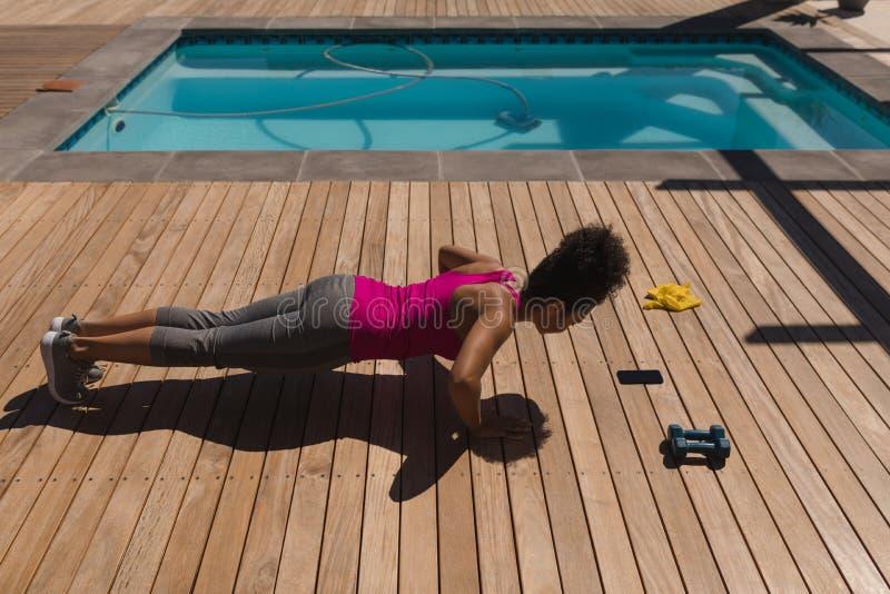 Vrouw die opdrukoefeningoefening in de binnenplaats van huis uitvoeren royalty-vrije stock afbeeldingen