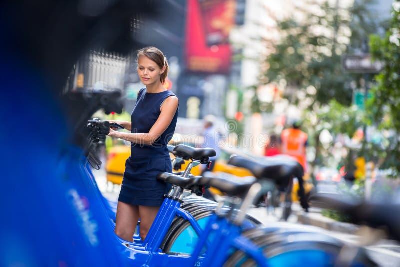 Vrouw die openbare stadsfiets nemen royalty-vrije stock foto
