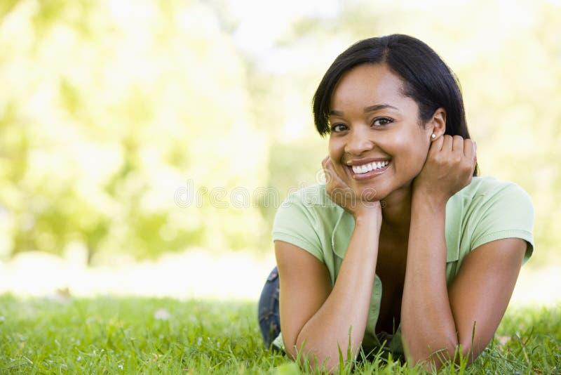 Vrouw die in openlucht glimlachend ligt stock afbeelding