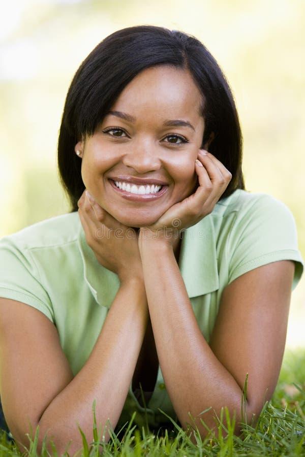 Vrouw die in openlucht glimlachend ligt stock afbeeldingen