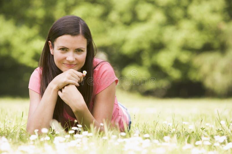 Vrouw die in openlucht met bloem het glimlachen ligt stock foto's