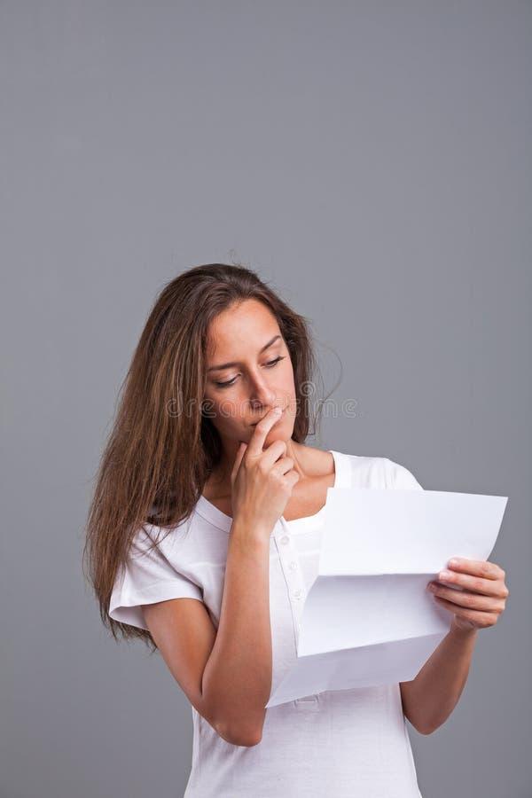 Vrouw die over die brief denken stock foto's