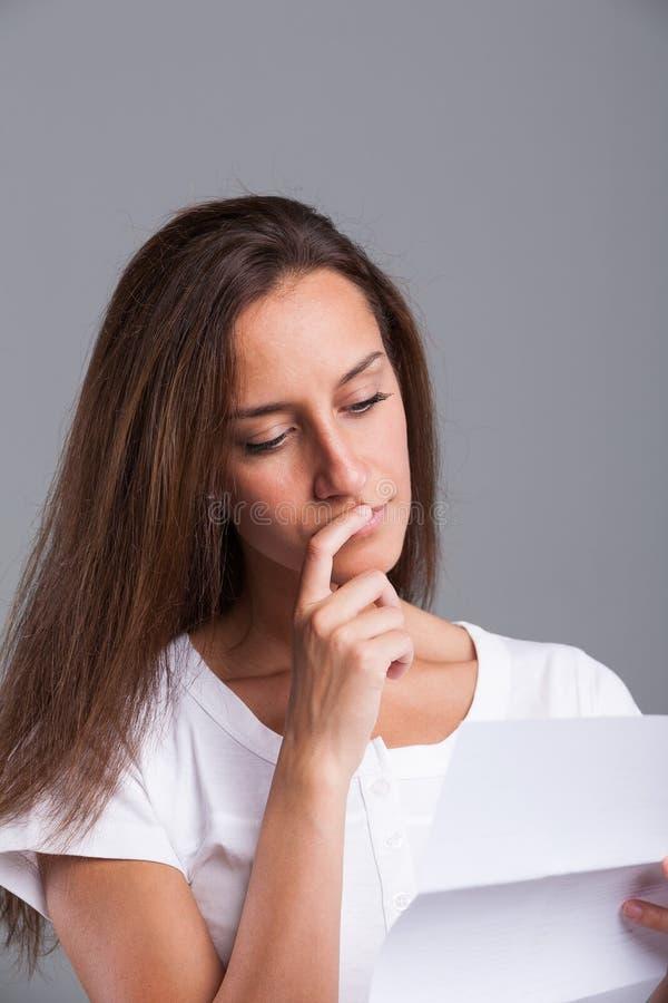 Vrouw die over die brief denken royalty-vrije stock afbeelding