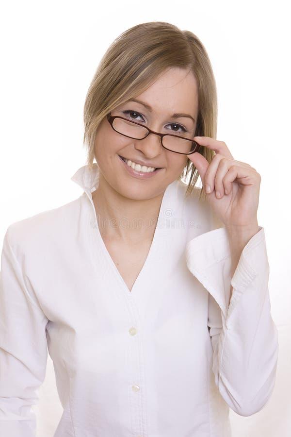 Vrouw die over de bovenkant van haar glazen kijkt stock fotografie
