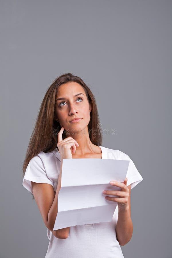 Vrouw die die of over de brief ongerust wordt gemaakt denken royalty-vrije stock fotografie