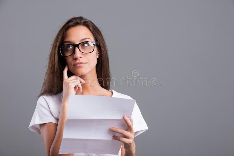 Vrouw die die of over de brief ongerust wordt gemaakt denken royalty-vrije stock foto's