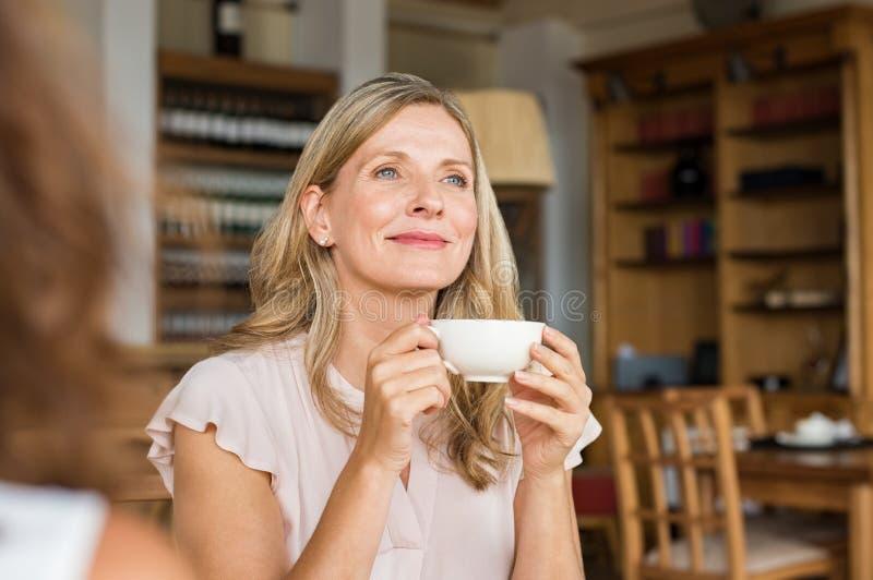 Vrouw die over koffie denken stock afbeeldingen