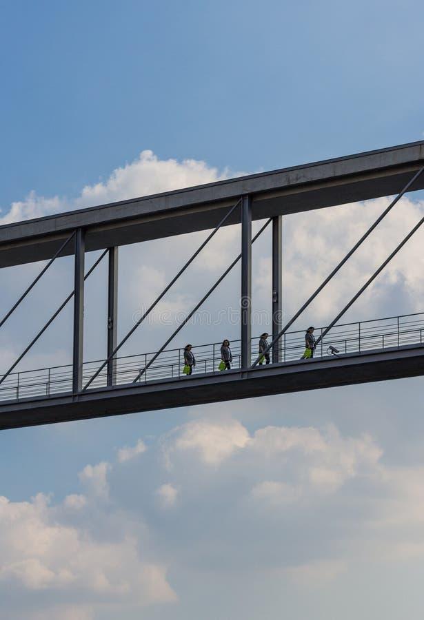 Vrouw die over moderne brug lopen - de achtergrond van de wolkenhemel stock afbeeldingen