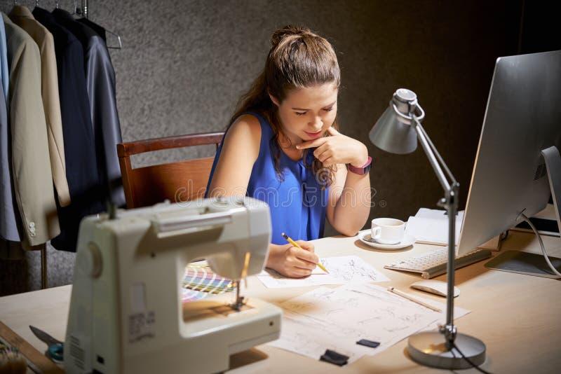 Vrouw die over nieuwe inzameling werken stock foto's