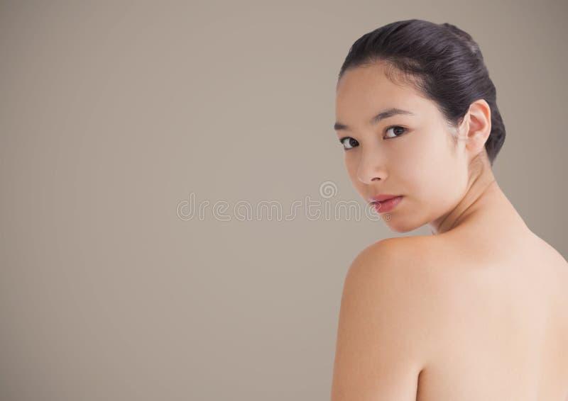 Vrouw die over schouder tegen bruine achtergrond kijken royalty-vrije stock afbeeldingen