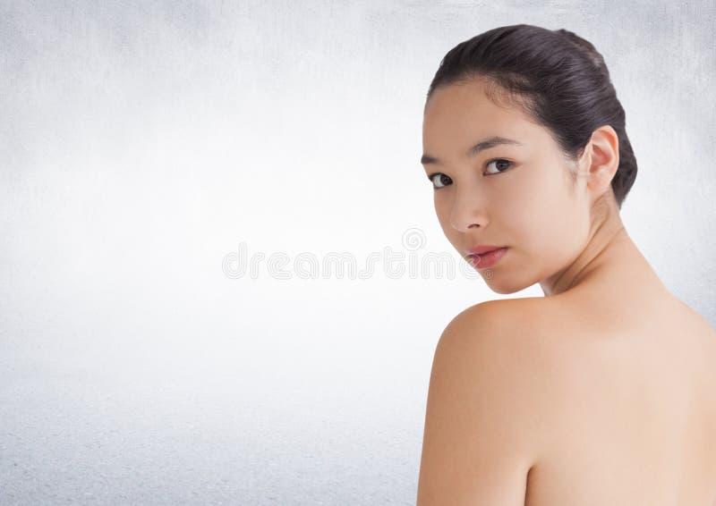 Vrouw die over schouder tegen witte muur kijken stock foto's