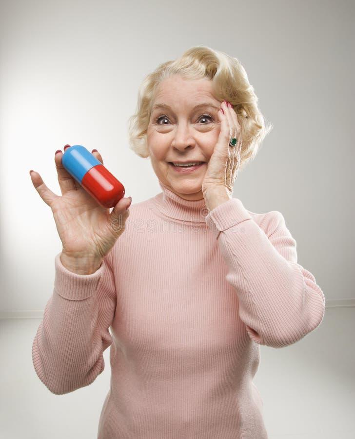 Vrouw die overmaatse pil houdt. stock foto