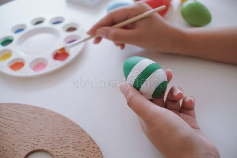 Vrouw die paaseieren thuis schilderen Familie die voor Pasen voorbereidingen treft stock fotografie