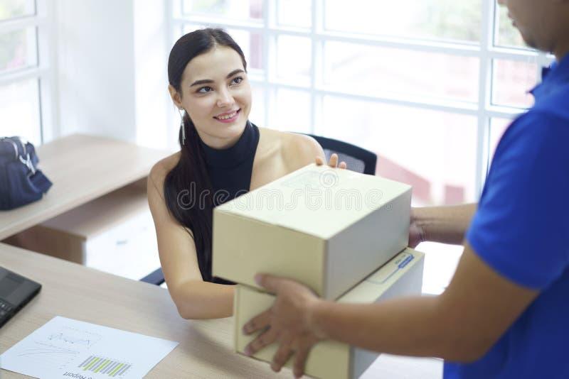 Vrouw die pakket van de leveringsmens ontvangen Van het de vrachtpakket van de leveringskoerier de dozen van het de verzendingska royalty-vrije stock foto