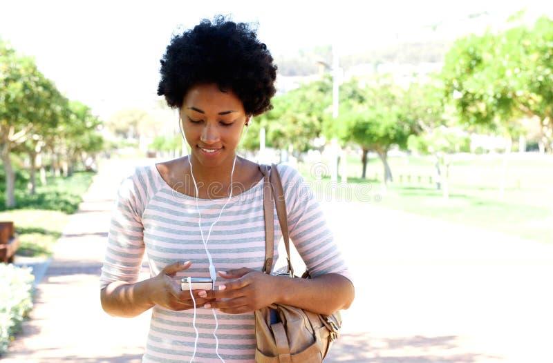 Vrouw die in park die aan muziek op telefoon lopen luisteren royalty-vrije stock foto