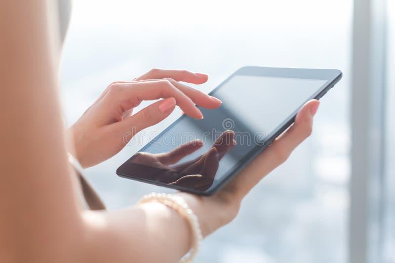 Vrouw die pdatoepassingen met WiFi Internet, wat betreft het scherm, het doorbladeren informatie, close-upbeeld gebruiken royalty-vrije stock foto's
