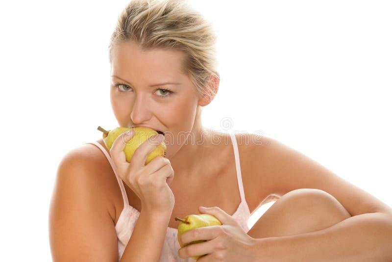 Vrouw die peer eet stock afbeelding