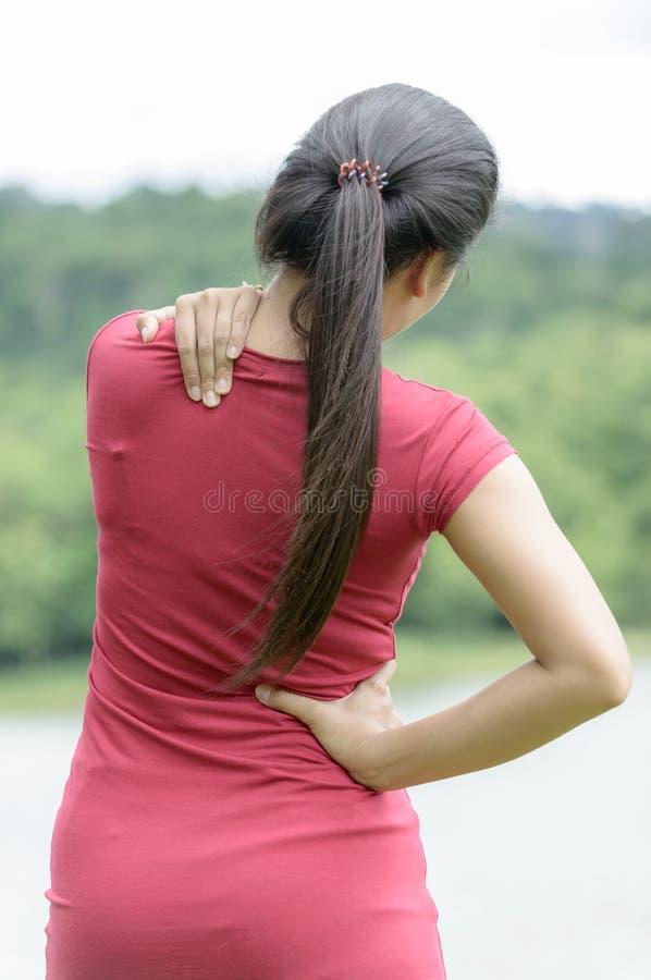 Vrouw die pijnrug masseert royalty-vrije stock afbeelding