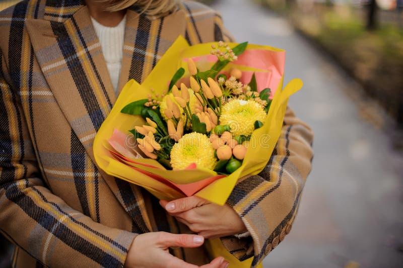 Vrouw die in plaidlaag een boeket van heldere gele bloemen houden royalty-vrije stock foto