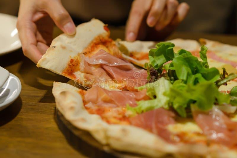 Vrouw die plak van verse de hampizza van Parma met de hand plukken royalty-vrije stock foto's