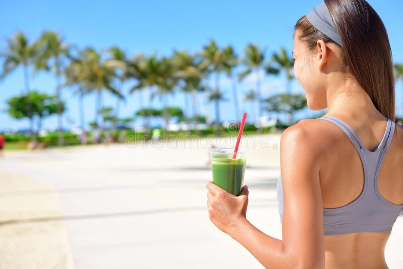 Vrouw die plantaardige Groene detox drinken smoothie stock afbeelding