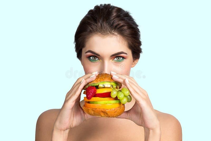 Vrouw die plantaardige hamburger eten stock foto