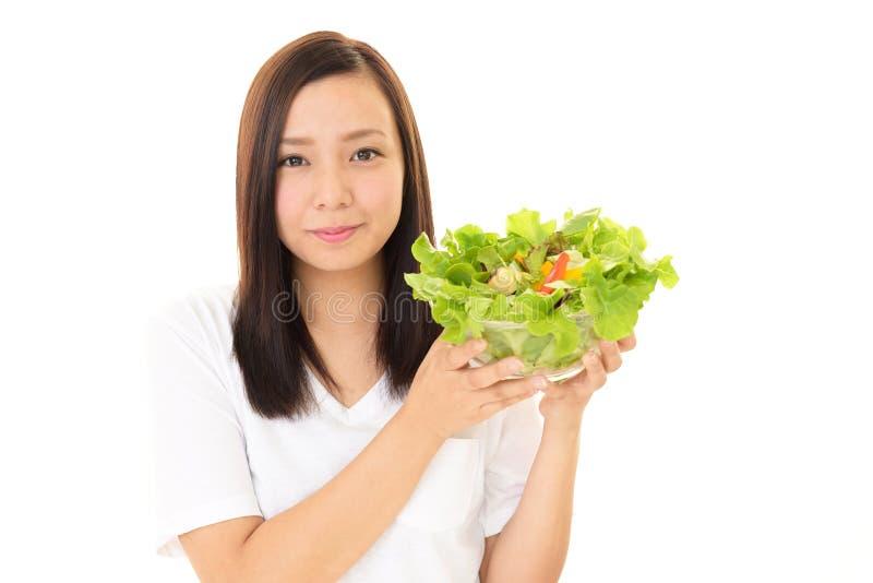 Vrouw die plantaardige salade eet stock foto