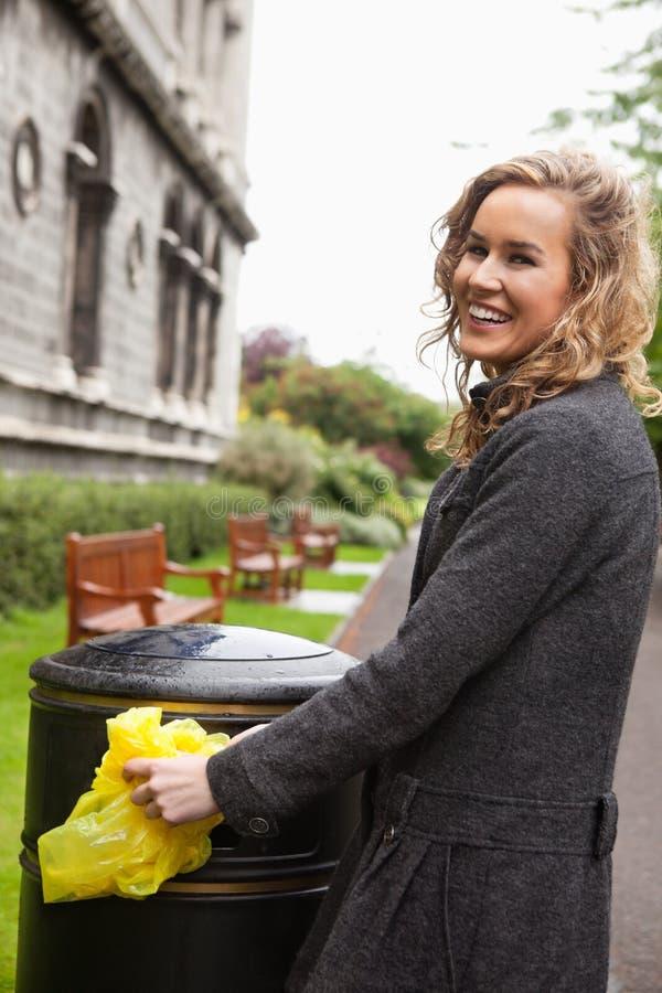 Vrouw die plastic afval in huisvuilbak zet royalty-vrije stock foto's