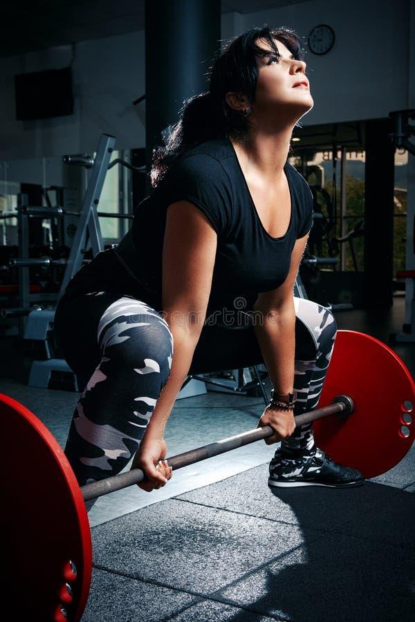 Vrouw die plus grootte in gymnastiek oefeningen met barbell doen powerlift, F stock afbeeldingen