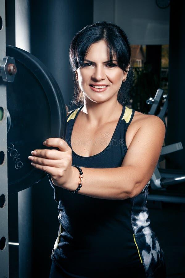Vrouw die plus grootte in gymnastiek oefeningen met barbell doen powerlift, F stock afbeelding