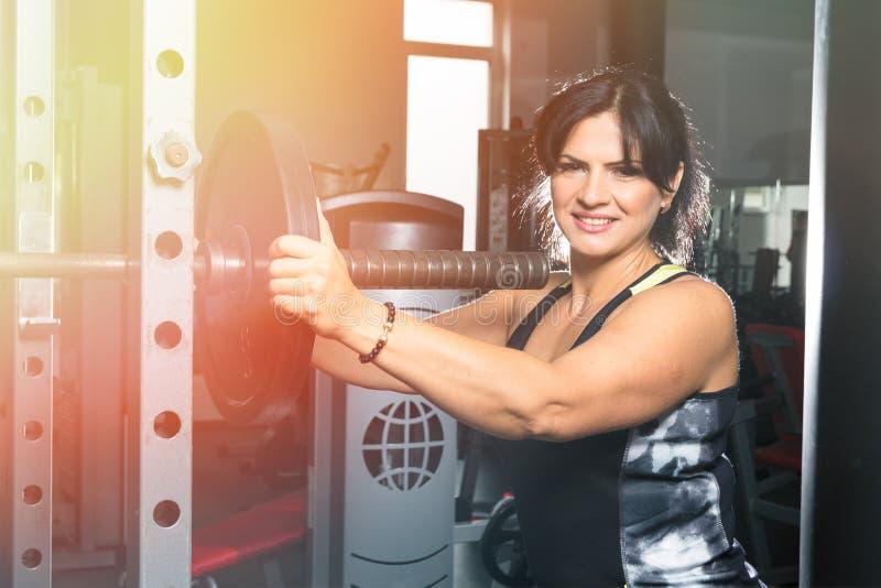 Vrouw die plus grootte in gymnastiek oefeningen met barbell doen powerlift, F royalty-vrije stock afbeelding